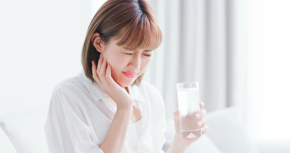 Lady with sensitive teeth reaction after drinking water - Brentwood Dental