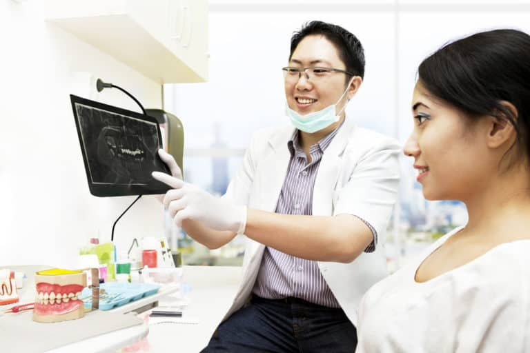 Dentists showing patient an X-Ray of her teeth - Brentwood Dental