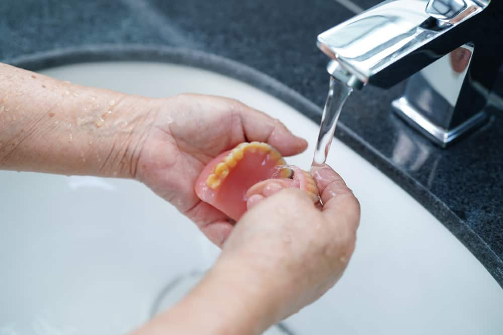 Man caring for new dentures by washing them - Brentwood Dental