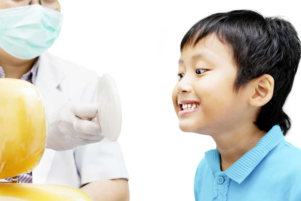 Child smiling in dentists mirror - Brentwood Dental