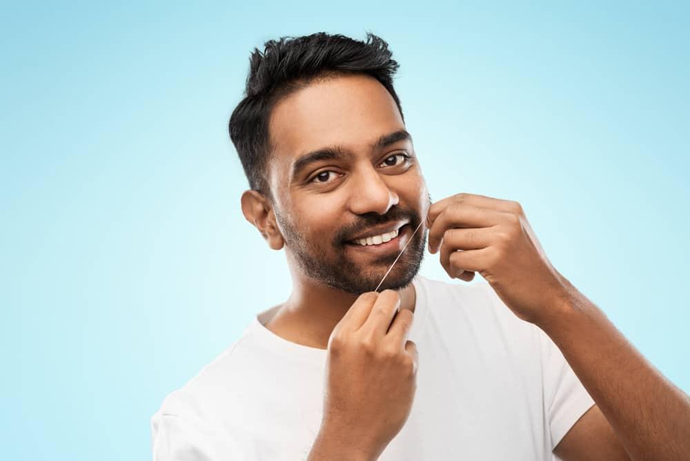 Man flossing teeth - Brentwood Dental
